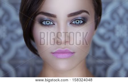 Closeup face of beautiful girl with silver smoky eye makeup and pink lips looking into the camera over gray vintage wall background