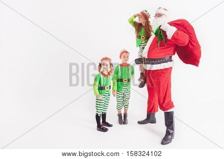 Christmas Wish 2016. Santa Claus and Little Kids dressed in Elven costumes. North Pole. Elf friend. Cristmas Scene at White Background. Santa Claus holding a Red bag with gifts. Looking for