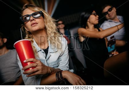 Young woman with cold drink and 3d glasses watching movie in theater. People in cinema watching 3d movie.