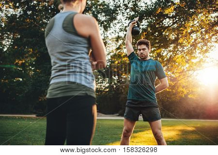 Young Man Doing Weight Training With Trainer