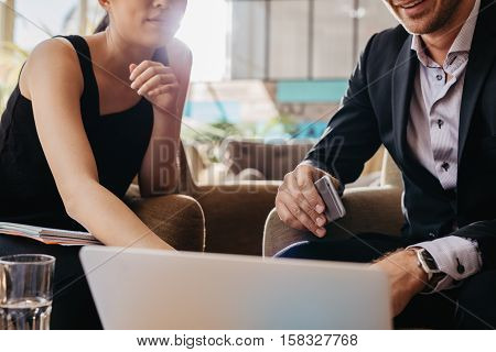 Shot of two young businesspeople sitting together working on laptop. Executives meeting in a office lobby. Man holding mobile phone and woman pointing at laptop screen.