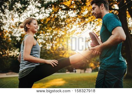 Personal Trainer With Woman Stretching In Park