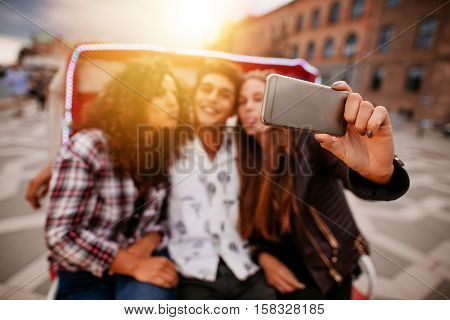 Young woman taking selfie on tricycle with friends. Young man and women riding on tricycle bike and taking self portrait. Focus on smart phone.