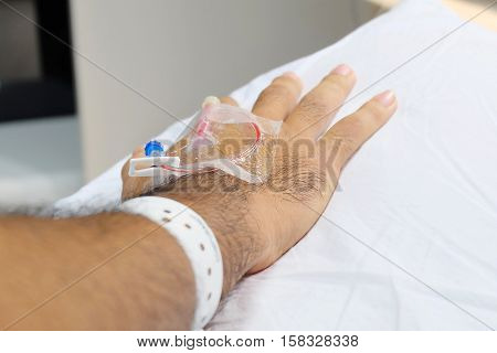 Asian male patients received saline drip in a hospital that is focused on the selection and copy space background with white pillow.