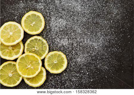 sliced lemons with sprinkled sugar on a dark grey background