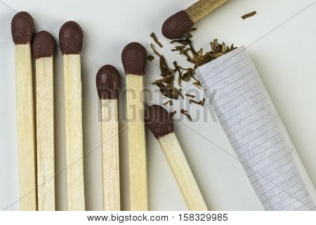 wooden matches and a rolling paper tobacco cigarette white background closeup