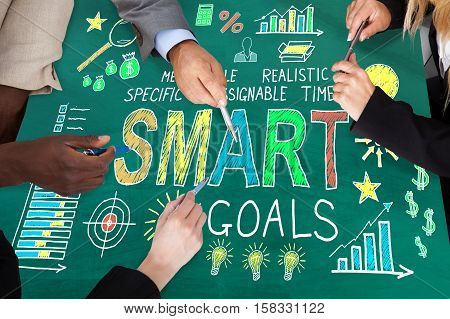 Group Of Businesspeople Holding Pen Discussing Smart Goal Concept Together On Blackboard
