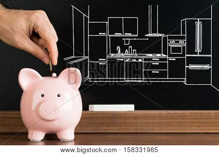 Close-up Of Person Inserting Coin In Piggybank With Kitchen Image Drawn On Blackboard In The Background