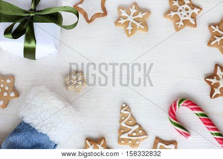 flat layout of festive cookies figure with a striped candy and gift top view / Christmas surprises from Santa's boot