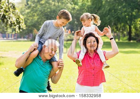 Happy Grandparents Giving Fun Piggyback Ride To Their Grandchildren In Park