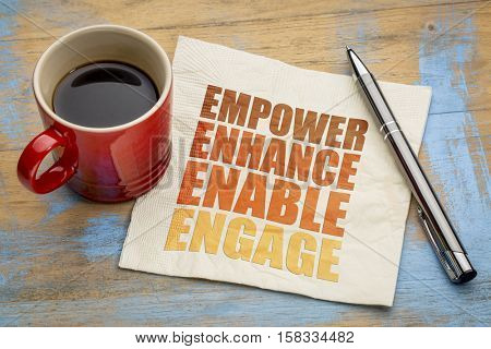 motivational leadership, coaching or business concept - empower, enhance, enable and engage  word abstract on a napkin with a cup of coffee