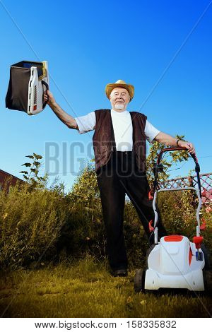 Happy retired senior man mows a lawn in his garden with a lawnmower.
