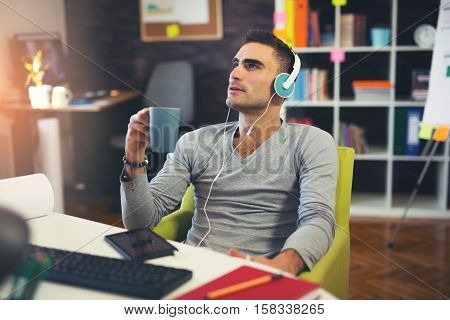 Creative businessman listening music at desk in office