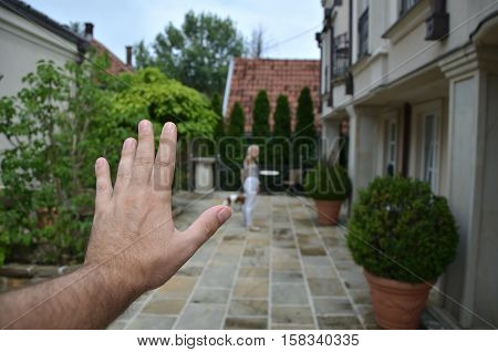Man's hand in a gesture of saying - good-buy - and a woman leaving with their dog