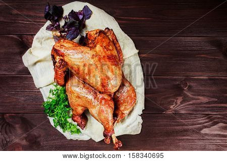 Roasted Turkey. Thanksgiving table served with turkey decorated with greens and basil on dark wooden background. Homemade roasted chicken. Christmas holiday dinner. Top view