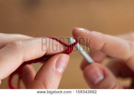 people and needlework concept - close up of hands knitting with crochet hook and red yarn poster
