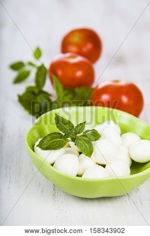 Mozzarella In A Green Plate On A Wooden Table. Mozzarella Balls With Basil Leaves And Tomato. Ingred