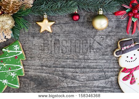 Snowman and christmas tree cookie with fir tree decorate with red and gold ornament on wooden table background with copy space for text Greeting card style for merry xmas and happy new year