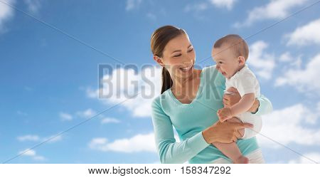 family, child and parenthood concept - happy smiling young mother with little baby over blue sky and clouds background