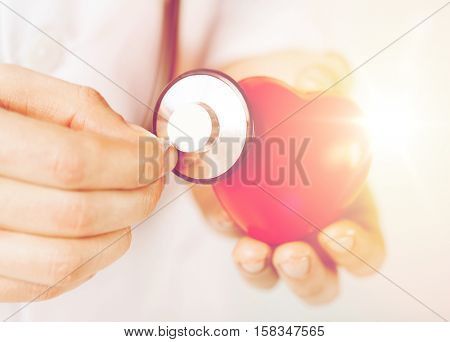 healthcare and medicine concept - close up of male hands holding red heart and stethoscope