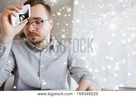 business, startup, stress, problem and people concept - businessman or creative male worker with smarphone at home office over snow