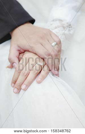 hand of groom and bride warming holding with wedding daimond ring