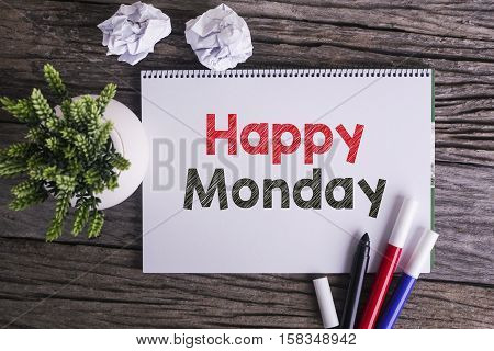 Notepad and green plant on wooden background with Happy Monday word
