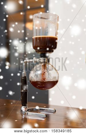 equipment and technology concept - close up of siphon vacuum coffee maker at shop over snow