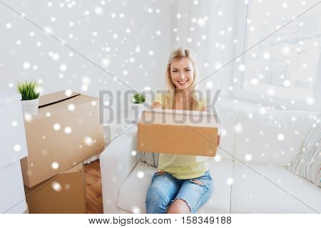 moving, delivery, accommodation and people concept - smiling young woman with cardboard box at home over snow