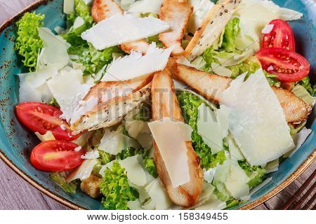 Salad with chicken breast parmesan cheese croutons tomatoes mixed greens lettuce and glass of wine on light wooden background. Ingredients on table