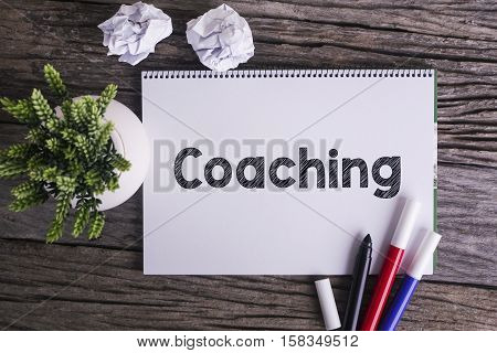 Notepad and green plant on wooden background with Coaching word