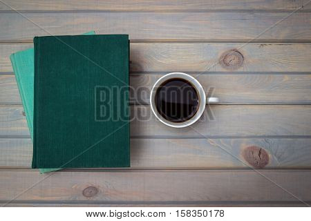 Green and blue books with a white porcelain cup of coffee on a gray wooden background.