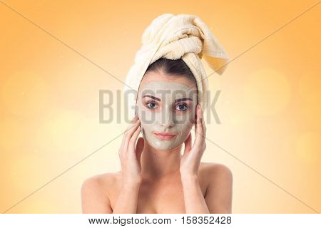 Young girl takes care her skin with cleansing mask on face and towel on head isolated on white background. Health care concept. Body care concept. Young woman with healthy skin.