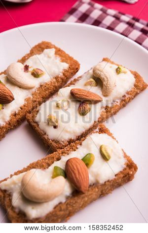 Shahi tukda prepared - deep fried bread in ghee, garnish with sweetened cream and dry fruits.