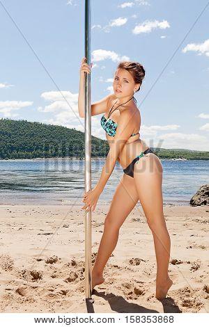 dancer in bathing suit on beach summer near pole
