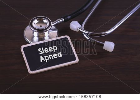 Medical Concept- Sleep Apnea words written on label tag with Stethoscope on wood background