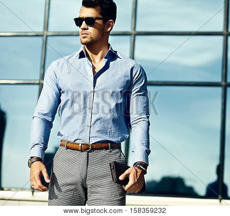 Fashion portrait of young handsome businessman model man in casual cloth in sunglasses in the street