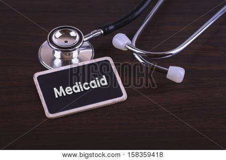 Medical Concept- Medicaid Words Written On Label Tag With Stethoscope On Wood Background.