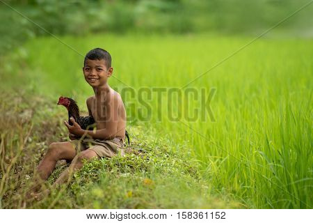 Little smiling boy farmer and chicken on green fields