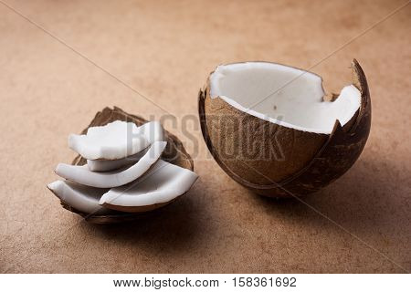 Coconut meat and shell on light brown background
