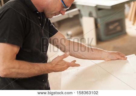 Artisan Working With Wooden Piece Of Furniture