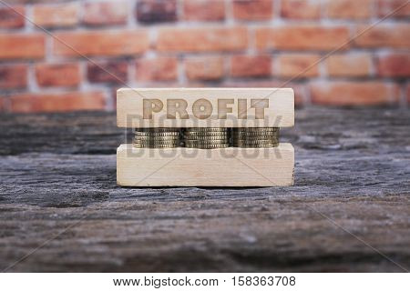 Business Concept - PROFIT word Golden coin stacked with wooden bar on shallow brick background