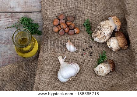 Mushrooms ceps with olive oil garlic herbs and nuts on wooden background