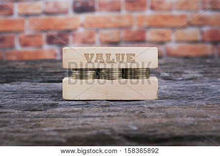 Business Concept - VALUE word Golden coin stacked with wooden bar on shallow brick background