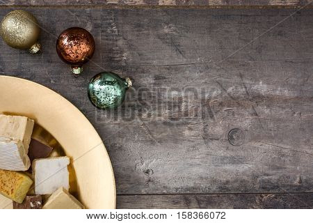 Christmas nougat on a golden plate on wooden background.Copyspace