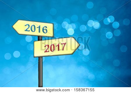 blue winter background with soft circles signpost with turn of the year 2016 to 2017