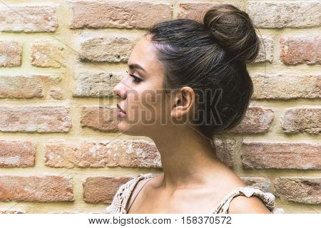 Close up profile portrait of an attractive pretty young woman chignon hairstyle - Stunning girl doing a serious expression - Pink and orange old wall in the background - Vintage filter