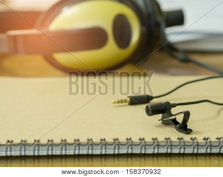 Clip Microphone On The Book And Headphones On The Table . Sounds Concept. Vintage Filter Effect.