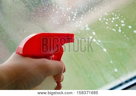 Hand Holding a Spray Bottle and Cleaning the Window