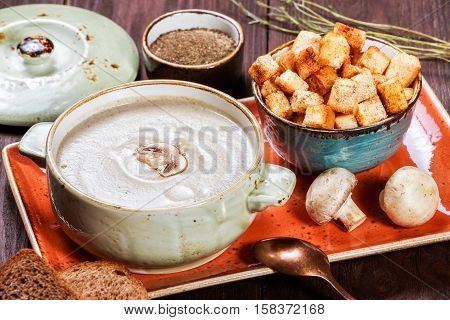 Cream soup with mushrooms herbs cream and crackers on plate on dark wooden background. Homemade food. Ingredients on table. Top view